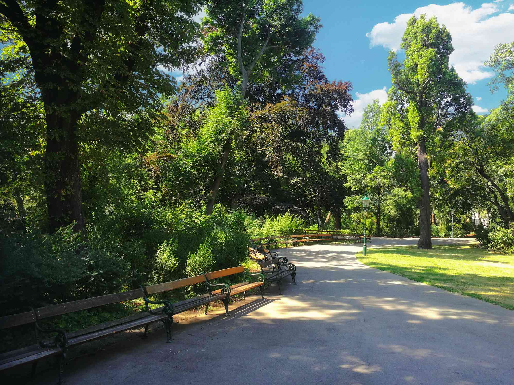 a walking path with several benches in the shade under large, green trees and small bushes at Vienna Stadtpark under a blue sky with white clouds on a summer day