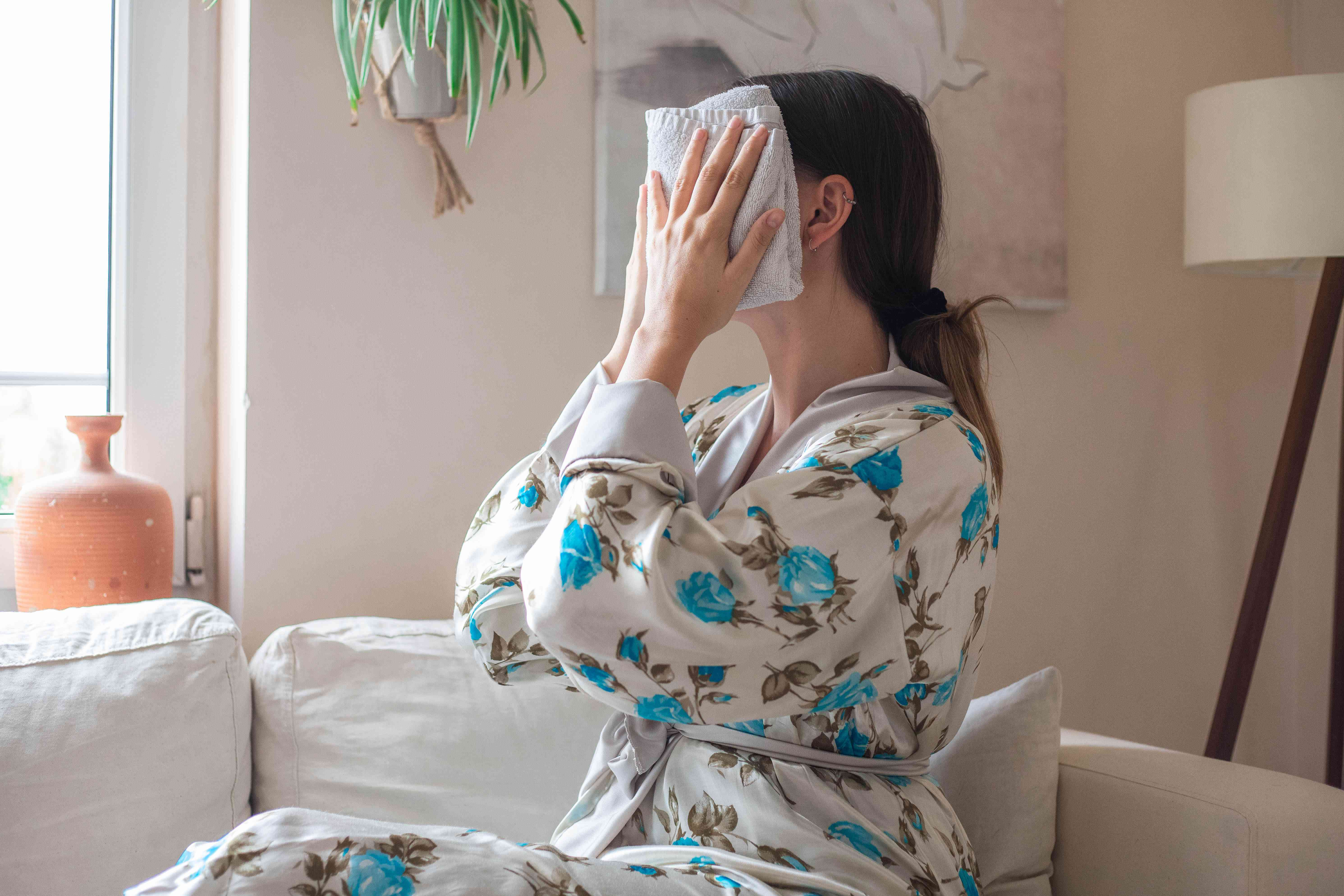 woman in floral robe places hot washcloth over face after oil cleansing