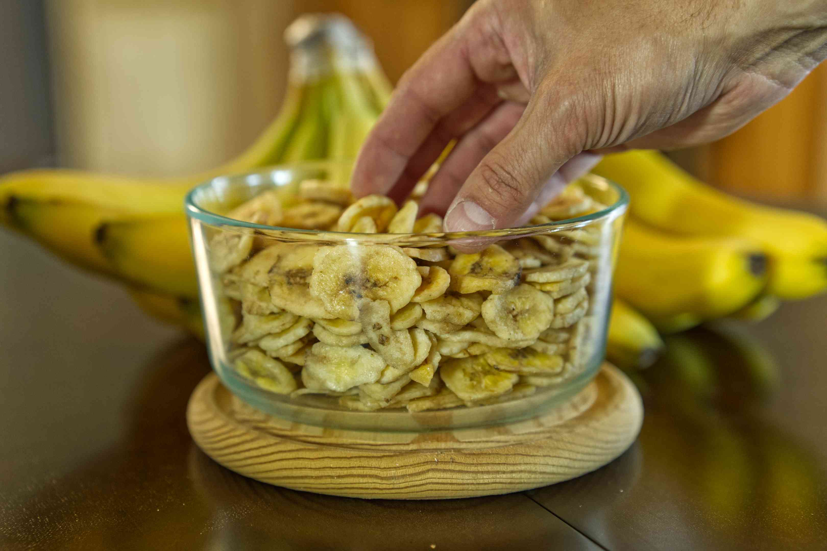 hand dips into glass jar of dried banana chips on table