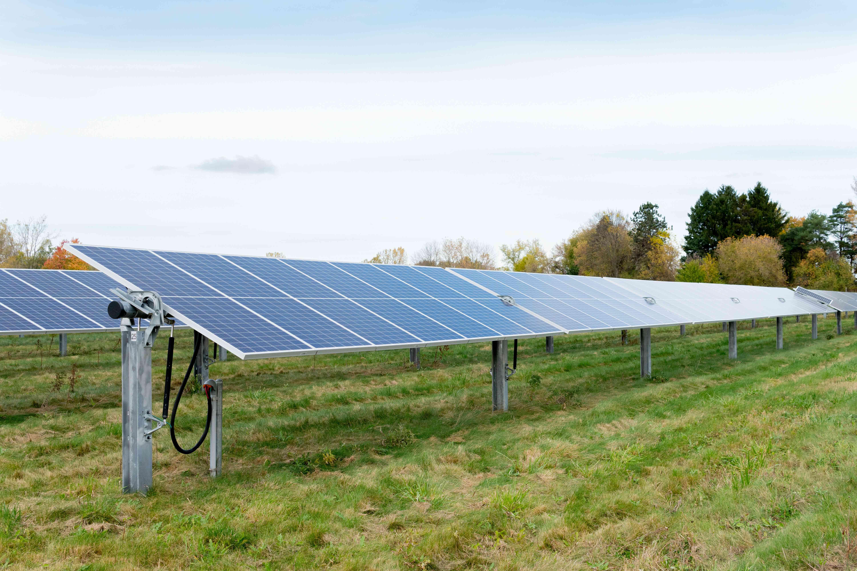 solar panels against big sky in green field