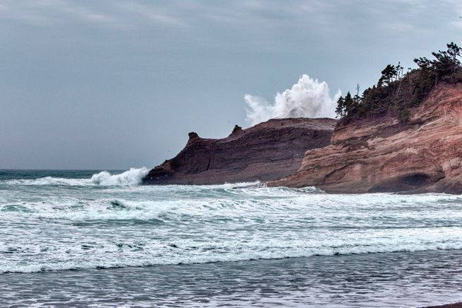 A wave crashes up against rocks near Cap Kiwanda along the Oregon coast