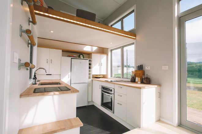 Tiny home Kitchen with counters on both walls and cupboards and a fridge along the back wall