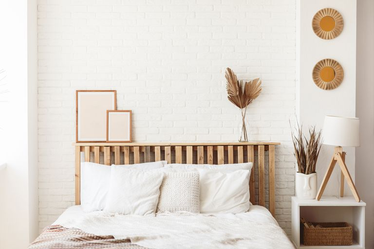 Wooden headboard with dry gold palm leaves in a glass vase and two photo frames on it. Stylish trendy decoration with copy space