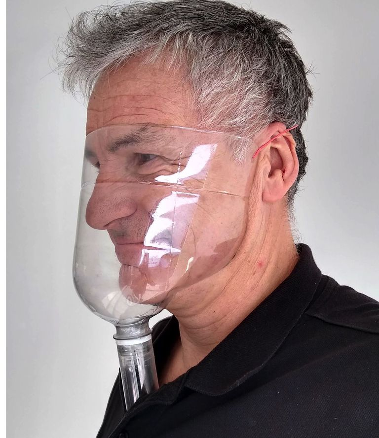 Gray-haired man with a clear plastic face shield
