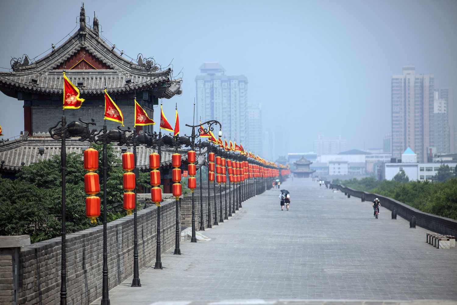People walk along the top of Xi'an City Wall on a smoggy day
