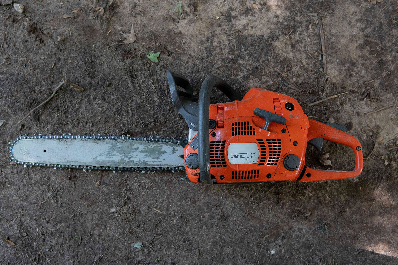 above shot of orange chainsaw on dirt ground