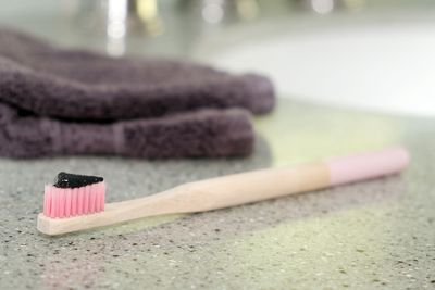 pink bamboo toothbrush with charcoal toothpaste on bathroom counter