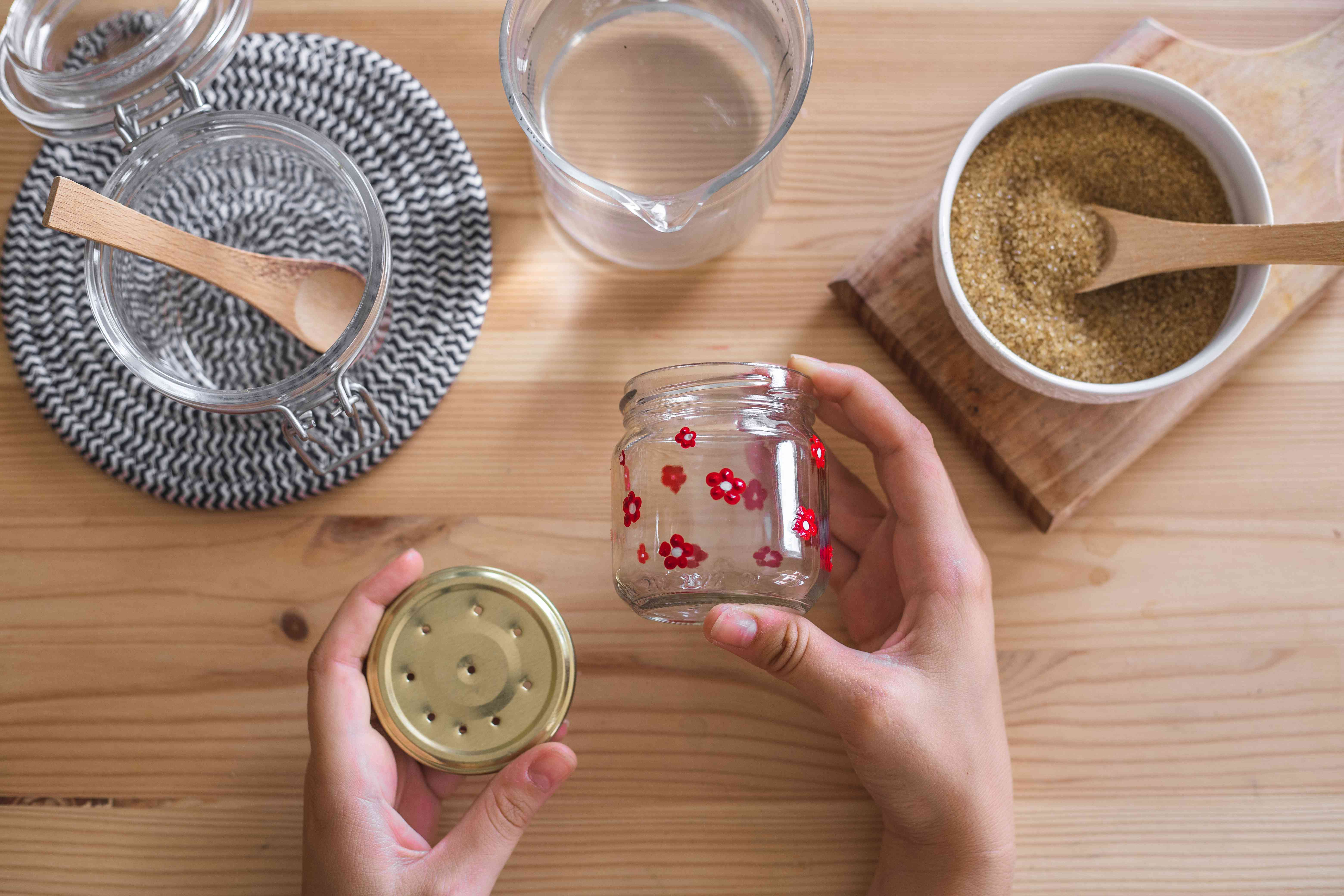 hands show diy glass jar feeder with lid surrounded by water and brown raw sugar