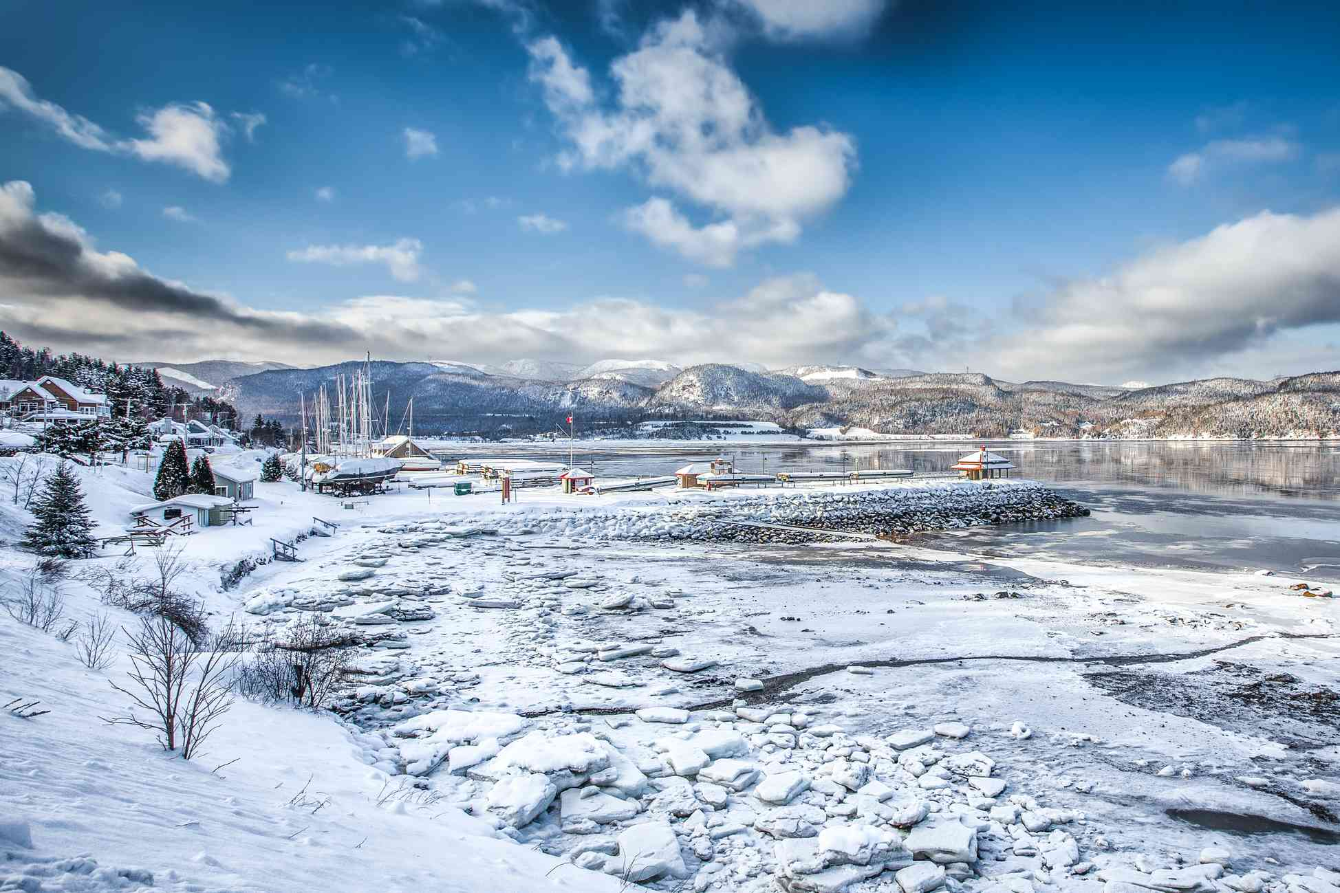 Snowy village and icy lake on the outskirts of Saguenay