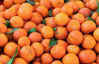 pile of fresh oranges with stem and leaves still attached