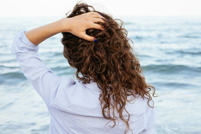 A woman with blue nails touches her healthy curly hair.