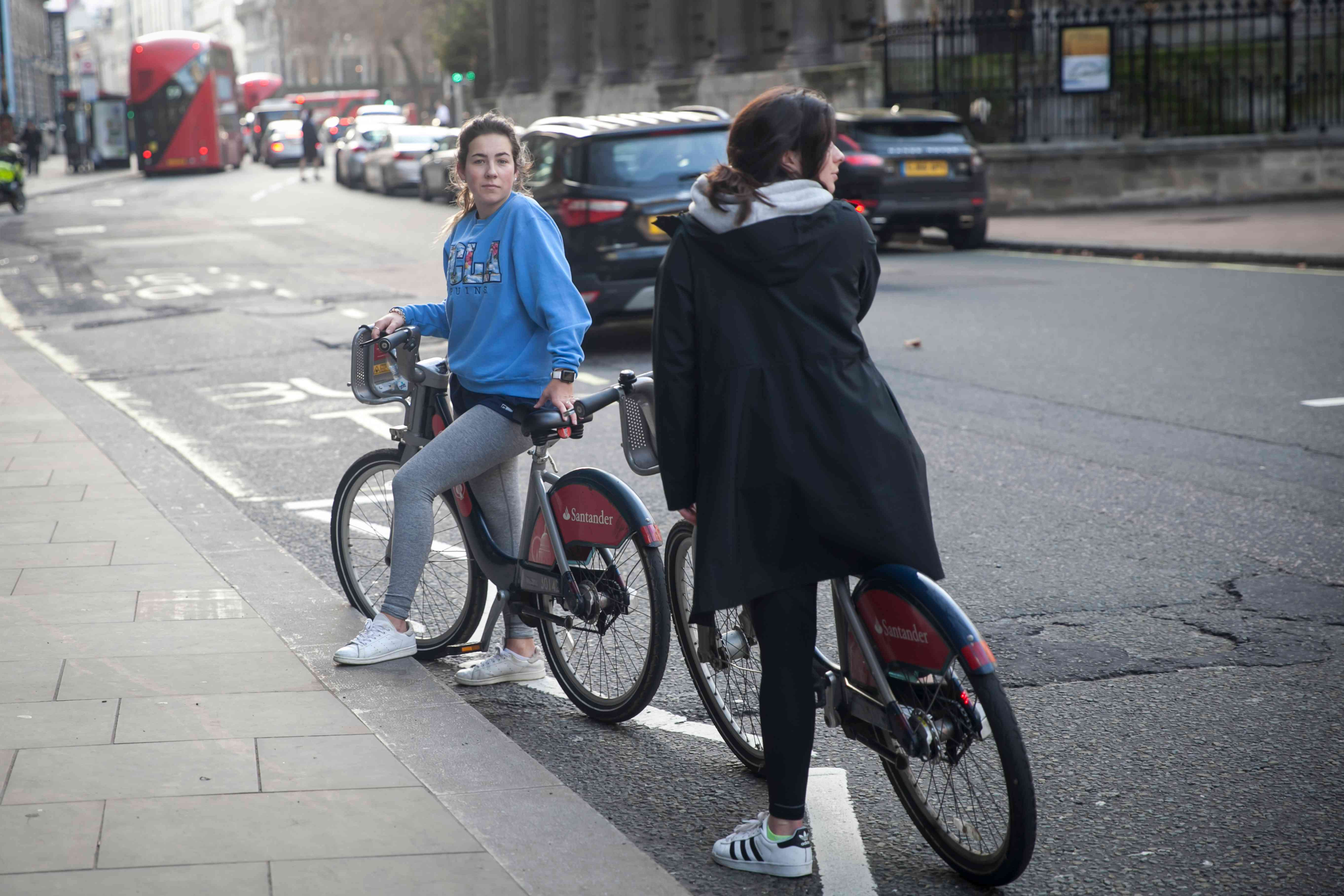 Young women on bikes chat on street in London surrounded by cars and buses