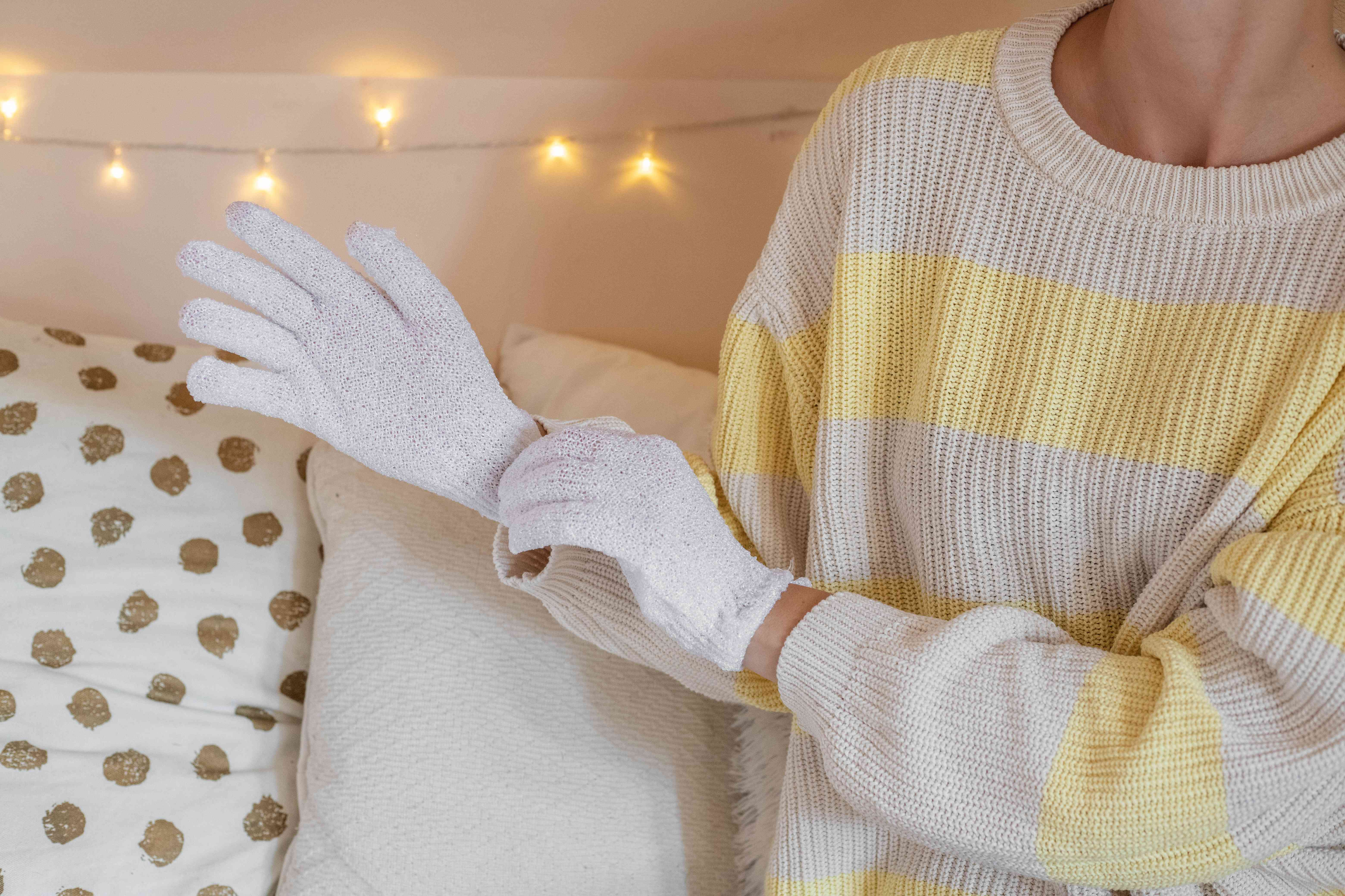 woman slips on white cotton gloves to lock in moisture before going to bed