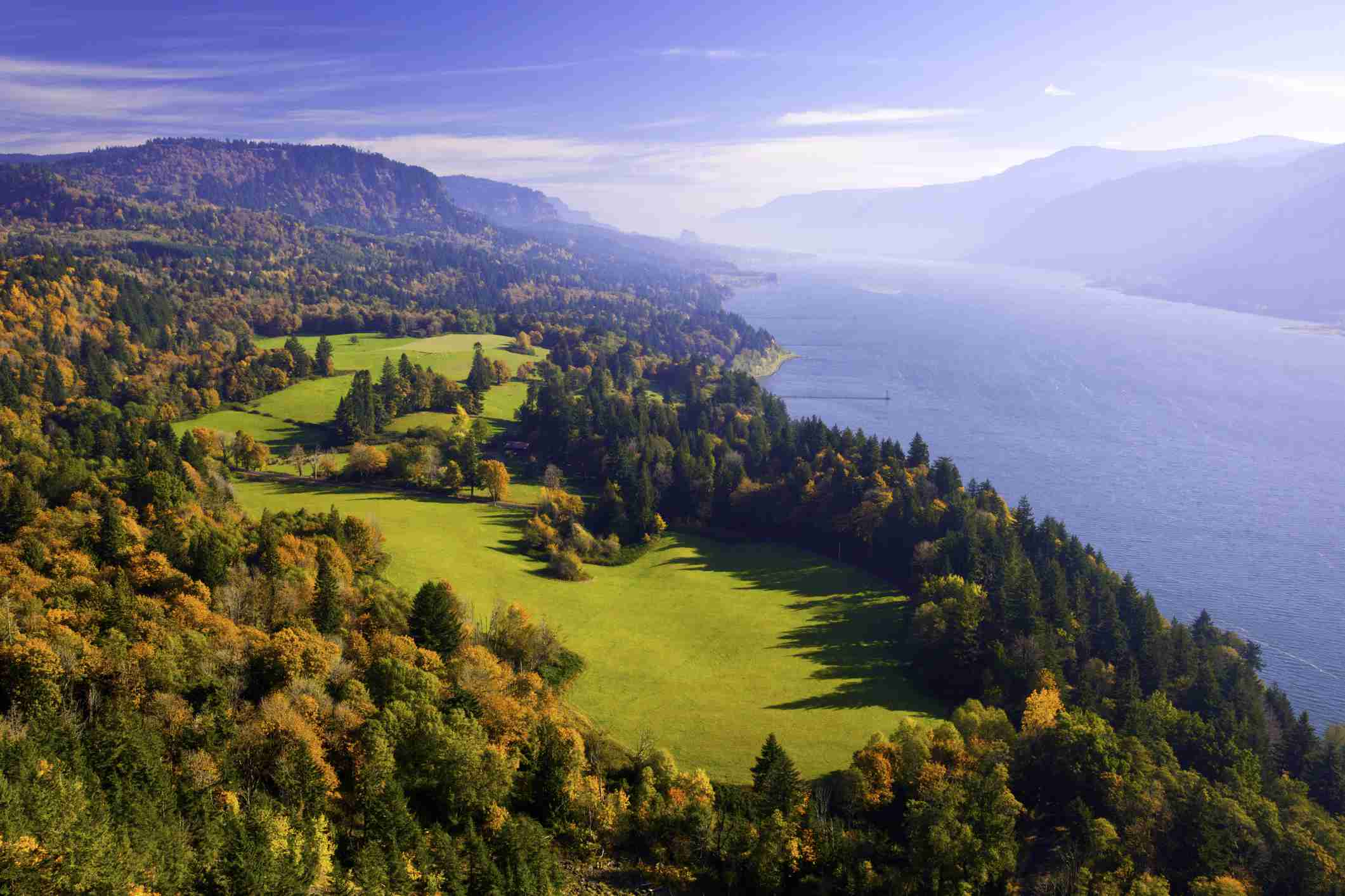 Aerial view of Cape Horn with a forest of trees in shades of gold, green, and orange surrounding a small patch of green grass adjacent to the Columbia River under a bright blue sky on a sunny day