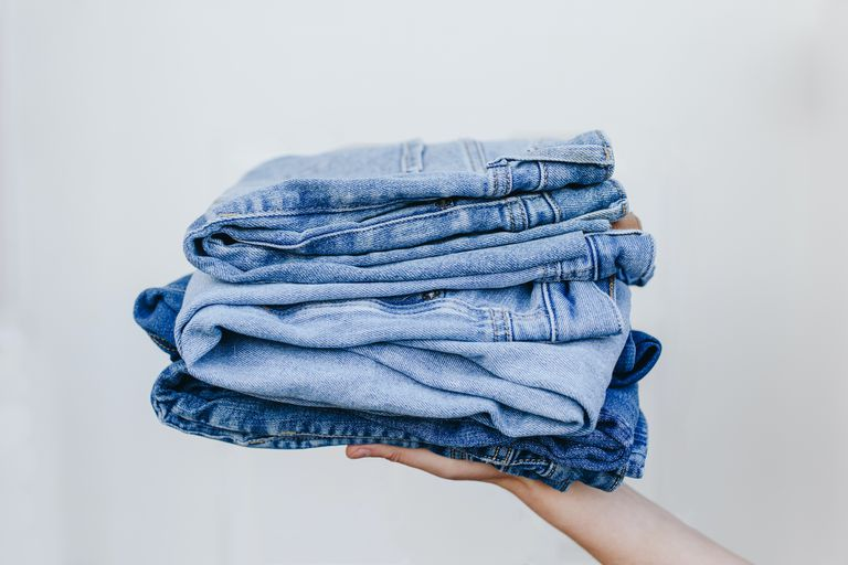 hand holds out multiple pairs of denim jeans stacked on top of each other in front of blank wall