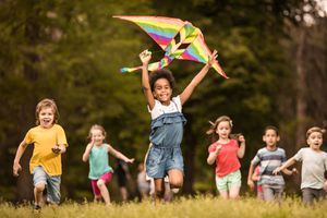 Large group of joyful kids running with a kite in springtime.