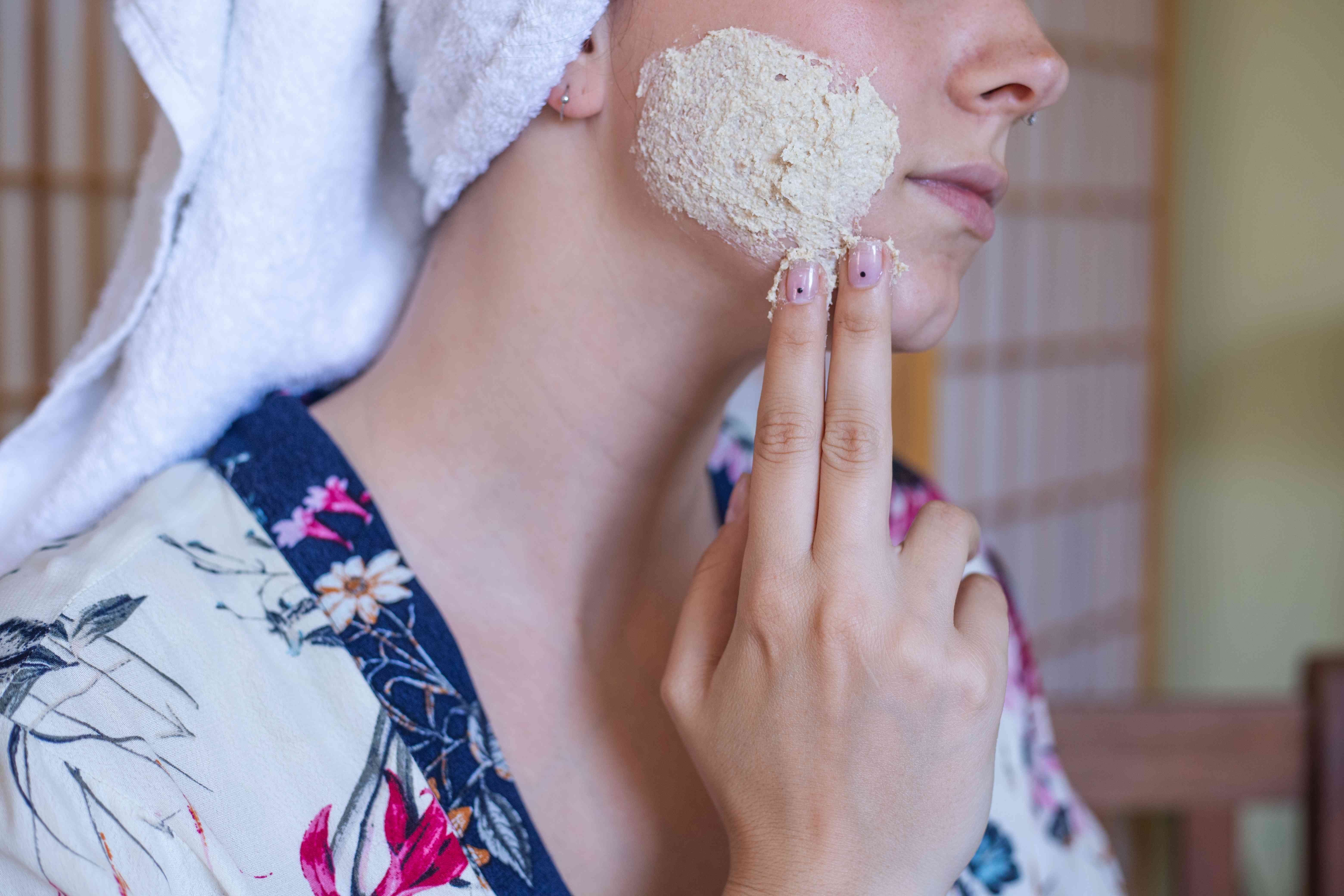 woman in silk robe with head wrap smears colloidal oatmeal paste on face