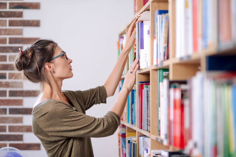 woman choosing books at library