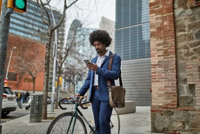 Businessman looking at his phone while standing next to his bicycle on the sidewalk