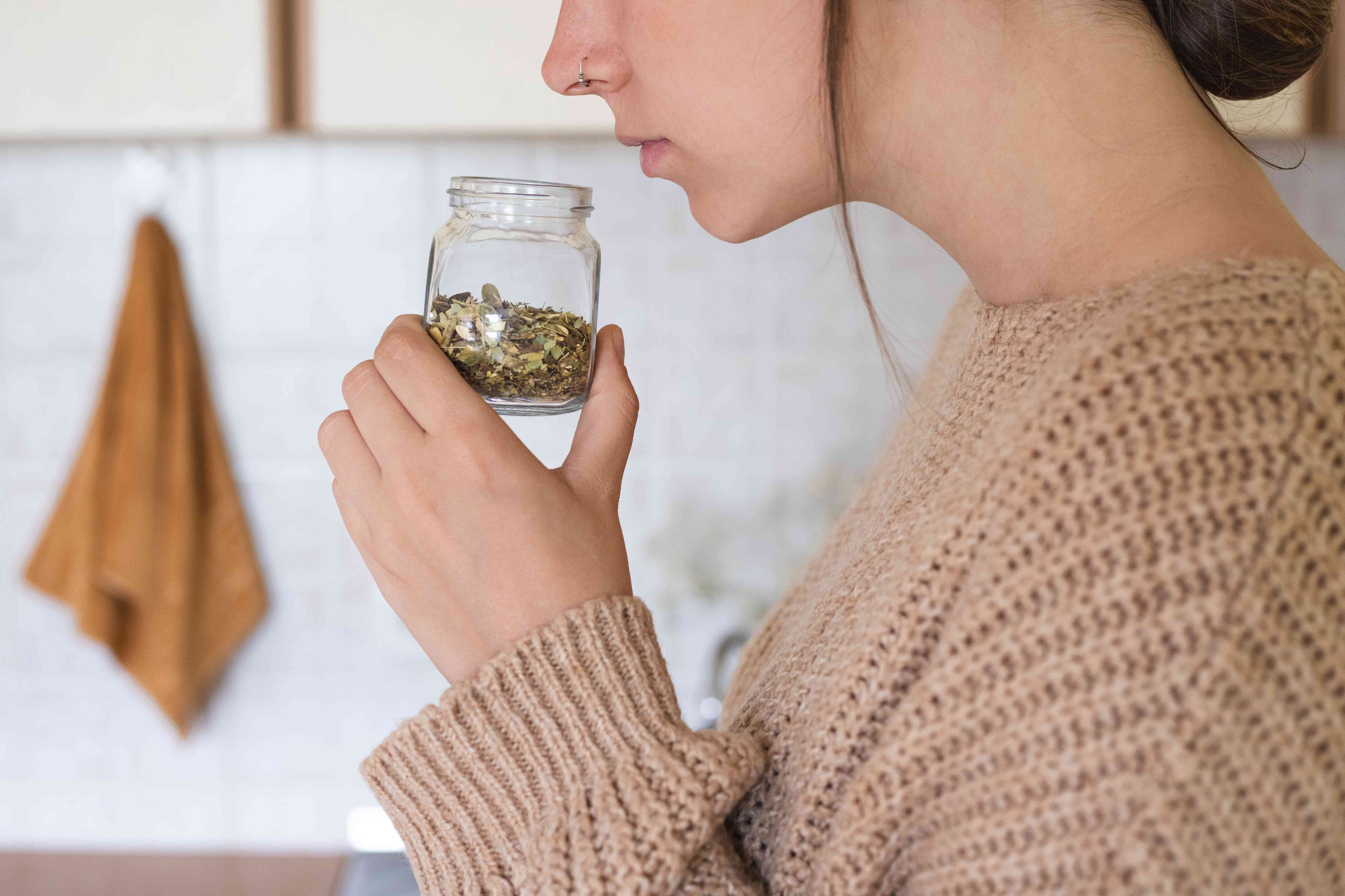 woman in sweater smells jar of dried spices to make sure it's still fresh