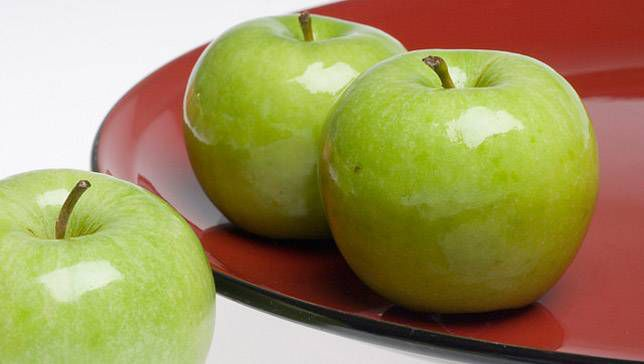 Granny Smith apples sitting on a red plate