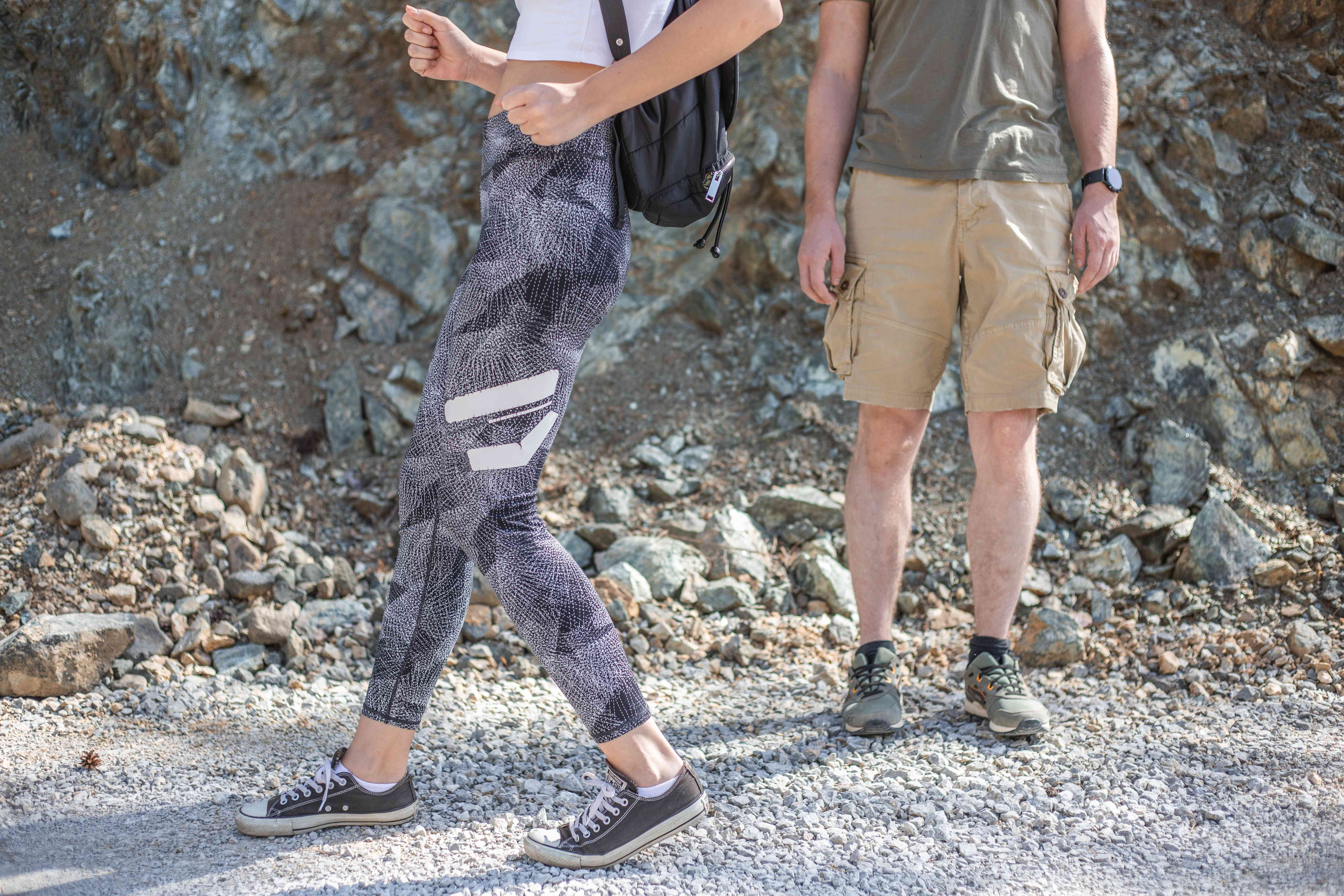 woman in workout clothes walks backward on gravel trail while exercise partner watches