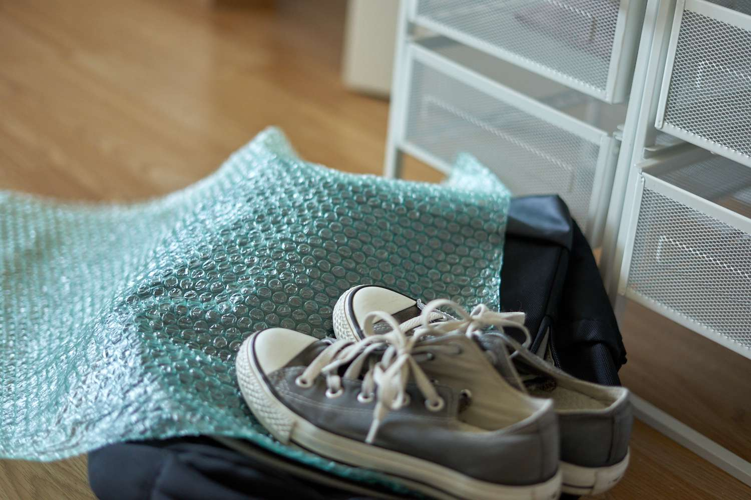 used piece of teal bubble wrap with old Converse sneakers and backpack