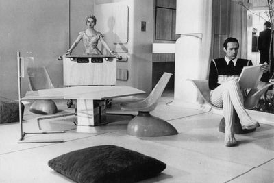 Black and white photo of a man and woman in a room with angular, futuristic furniture