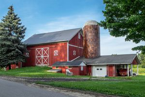 classic red barn with grain silo with large trees and blue sky
