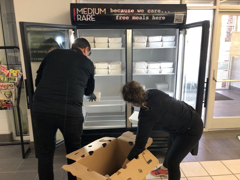 Volunteers stock a refrigerator with free meals.