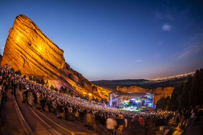 Sunset with a clear blue sky behind the lit stage, audience, and red rocks at Red Rocks Amiptheatre