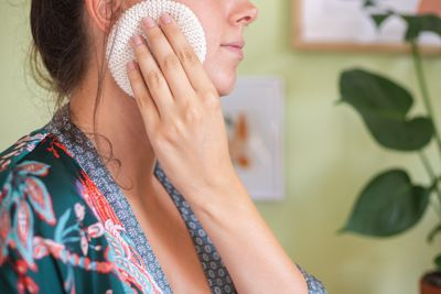 woman cleans face with reusable white cloth pad while wearing silky robe