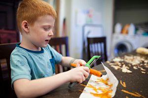 little boy peels carrots