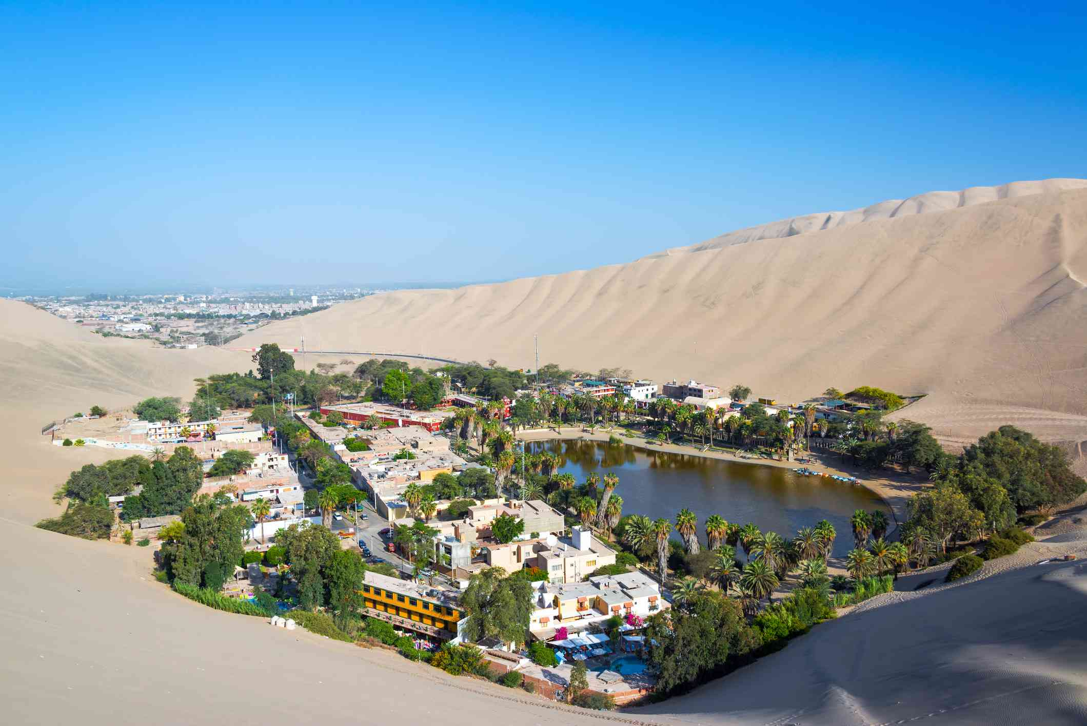 Huacachina oasis, ringed with green trees and surrounded by sand, with Ica, Peru in the Background