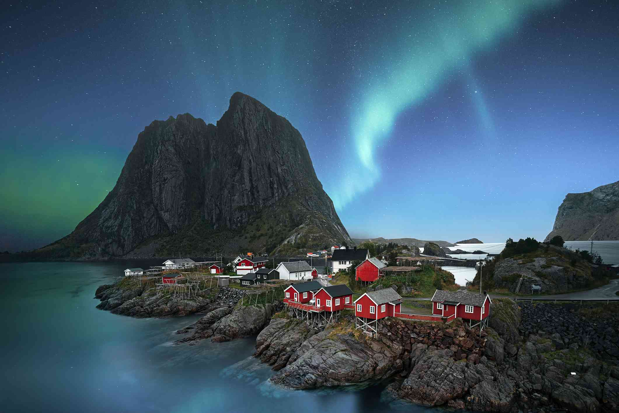 Northern lights appearing at dawn over small village in Norway