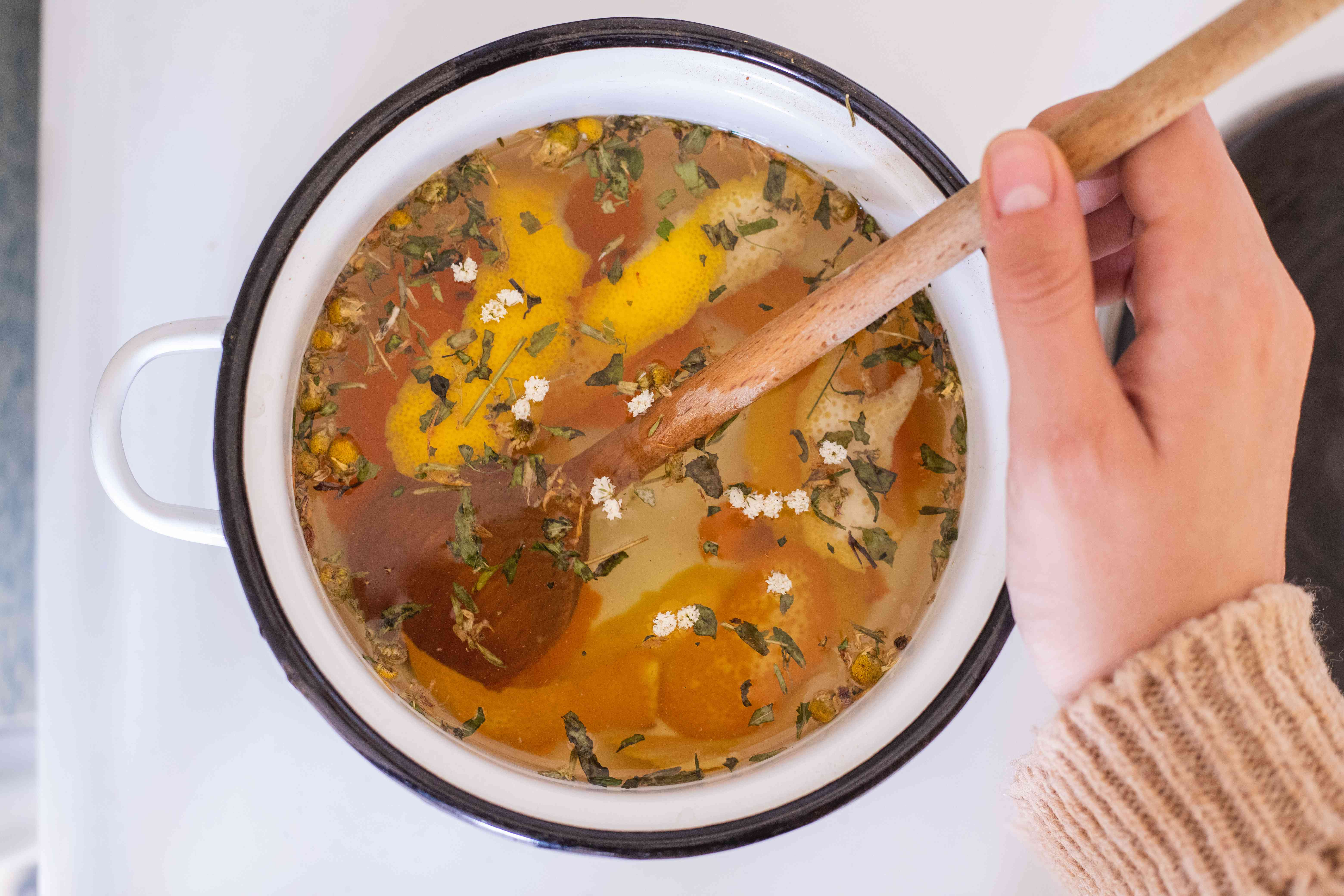 hand stirs pot of warm water and expired spices to make a fragrant potpourri on stove