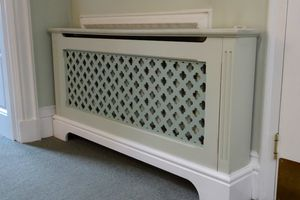 White wooden radiator cover with clover-shaped vents