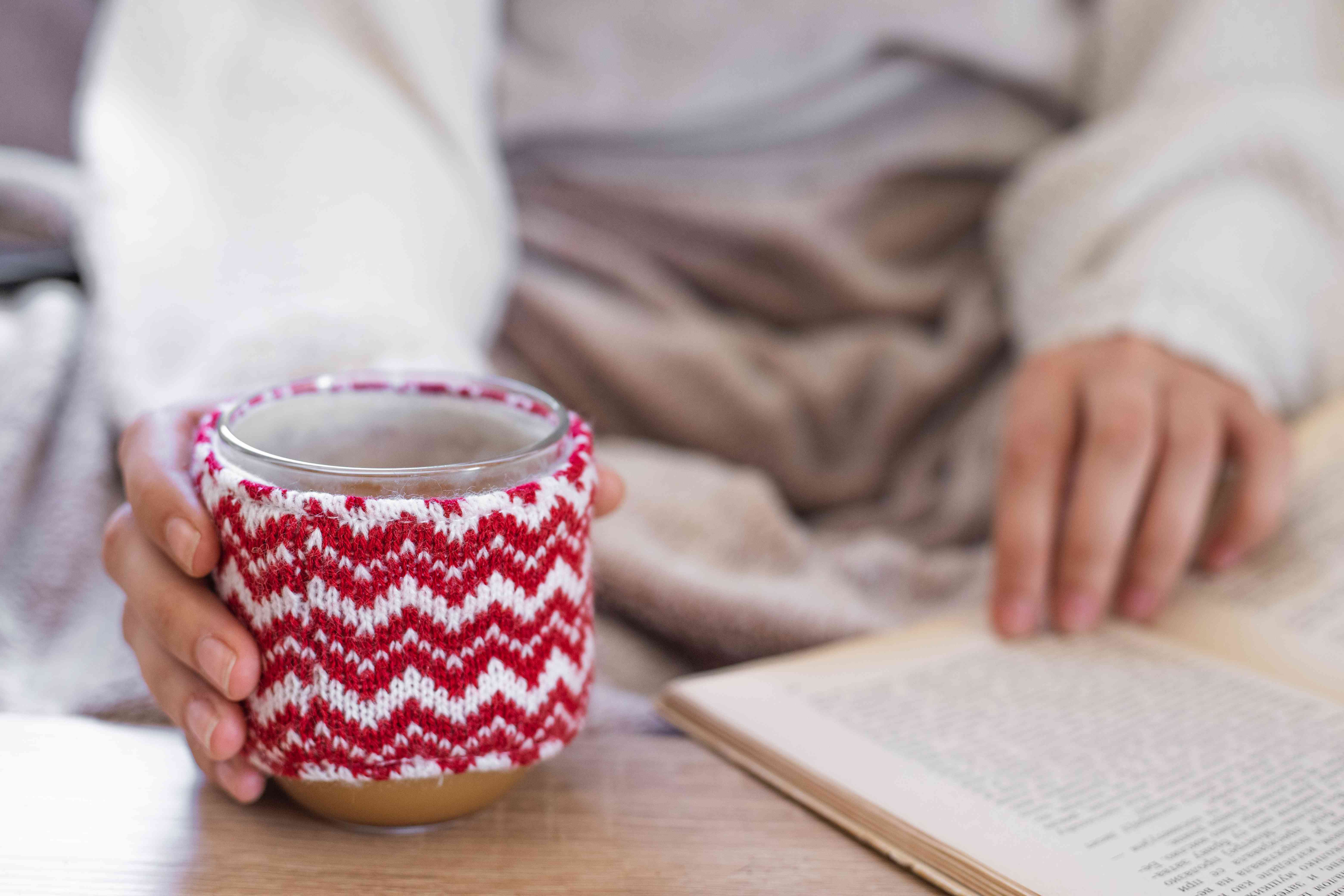 person holds hot beverage in red-and-white sweater cozy while reading book