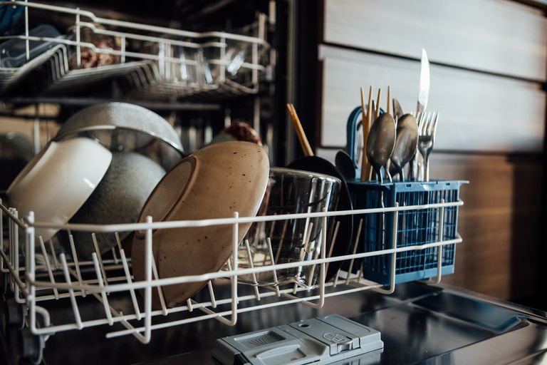 Bowls and utensils in the bottom rack of a dishwasher