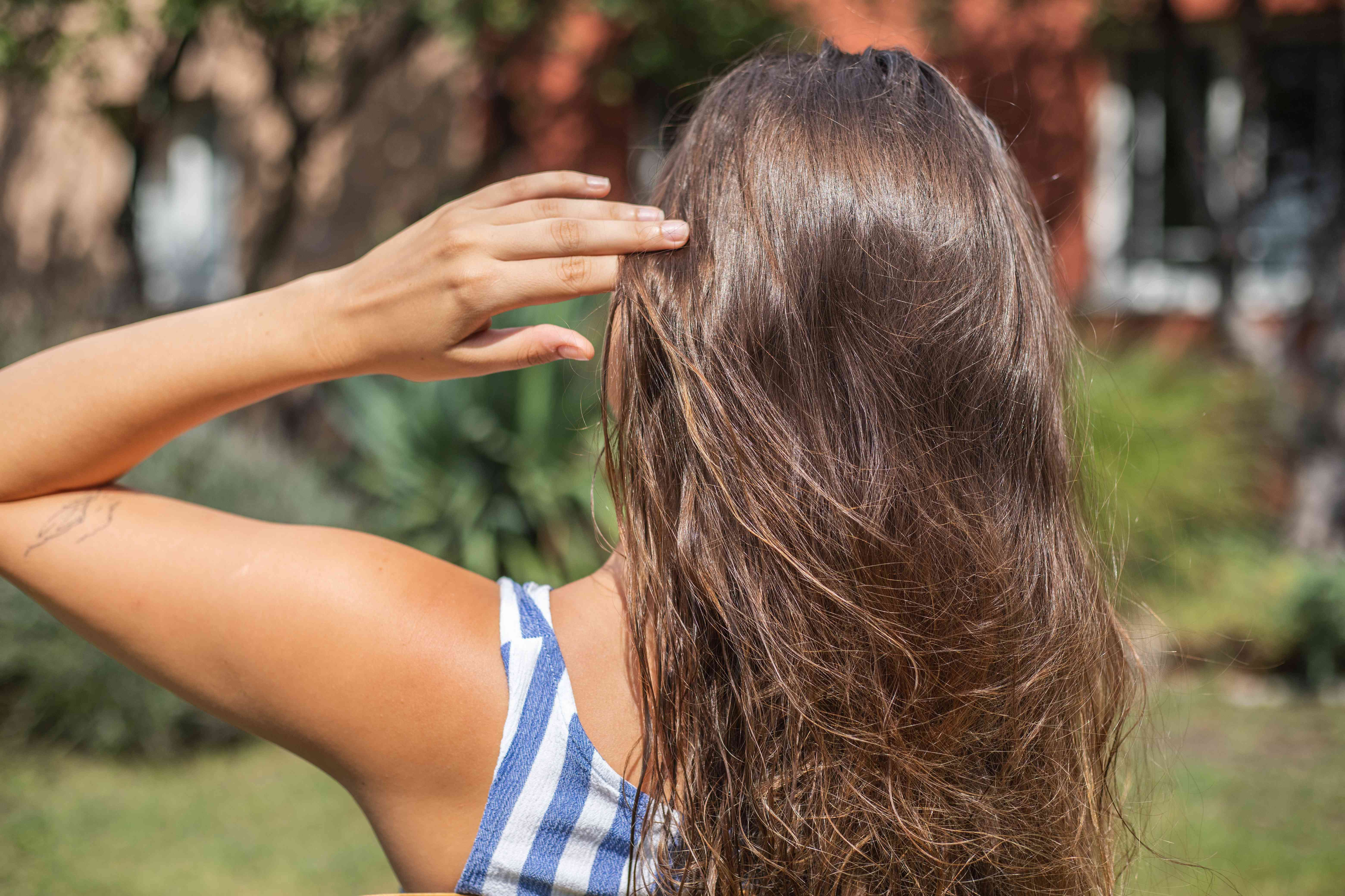 back of woman in striped tank showing off long shiny brown hair glowing in sun