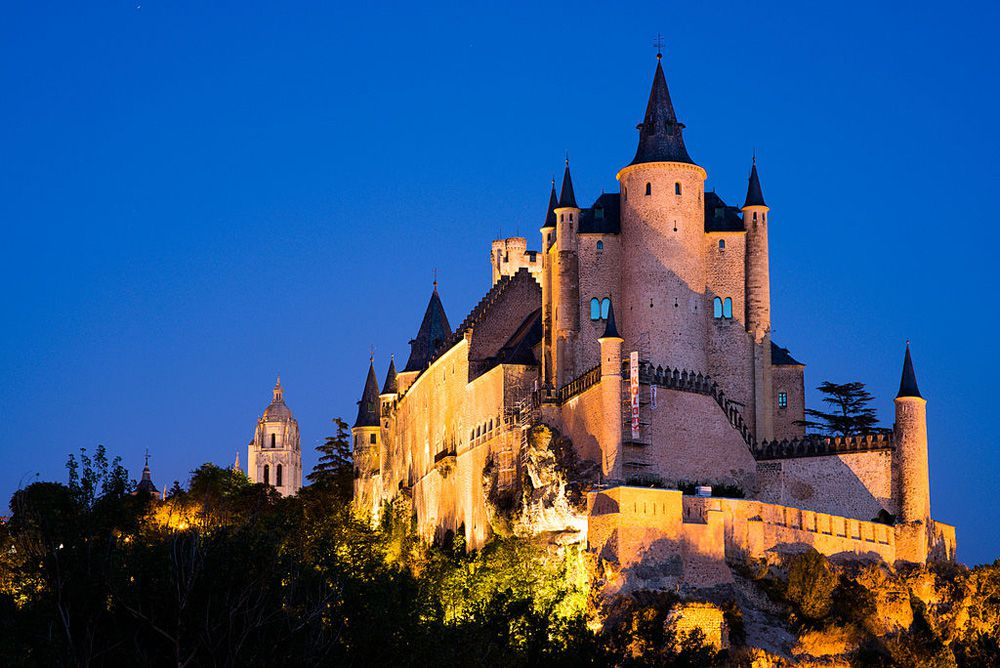 View of Alcazar de Segovia castle illuminated on the front and left sides at twilight under a clear blue sky