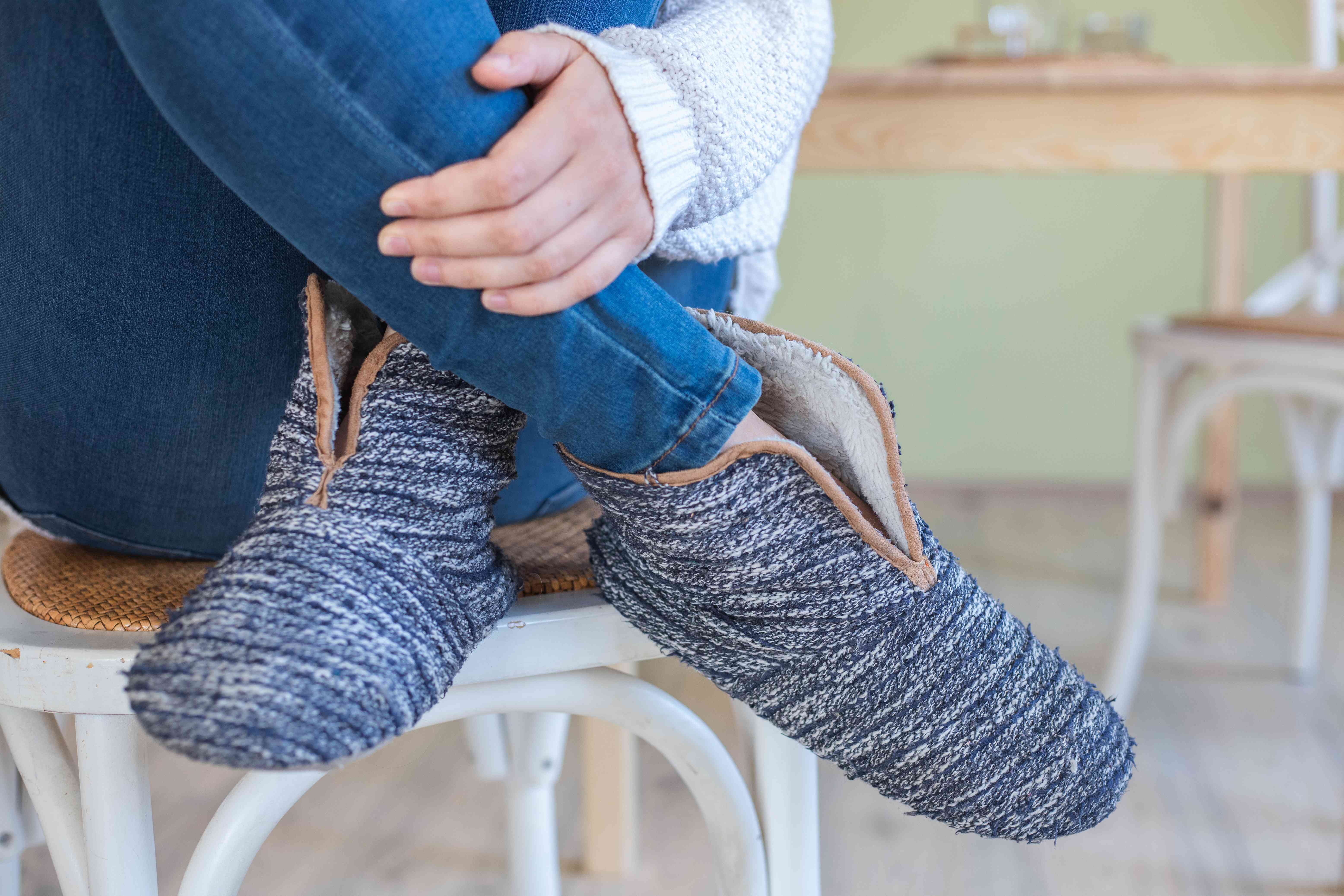 old sweater slippers modeled by woman in jeans who sits on white chair
