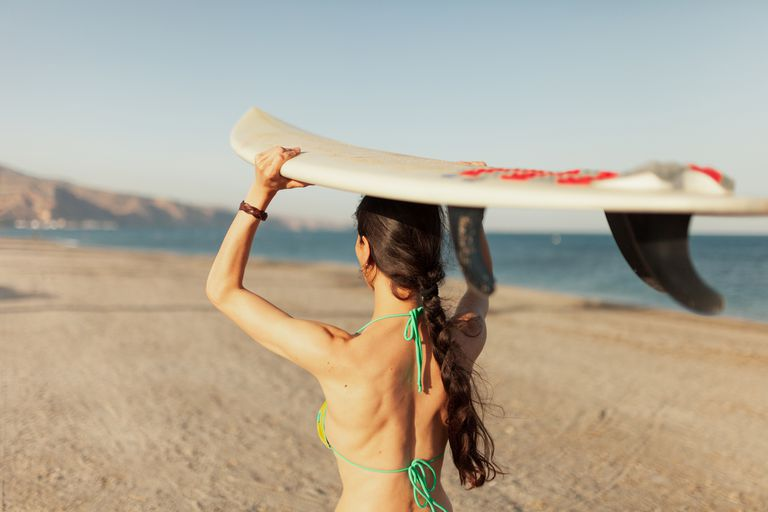Woman walking on the beach carrying her surf board propped on her head