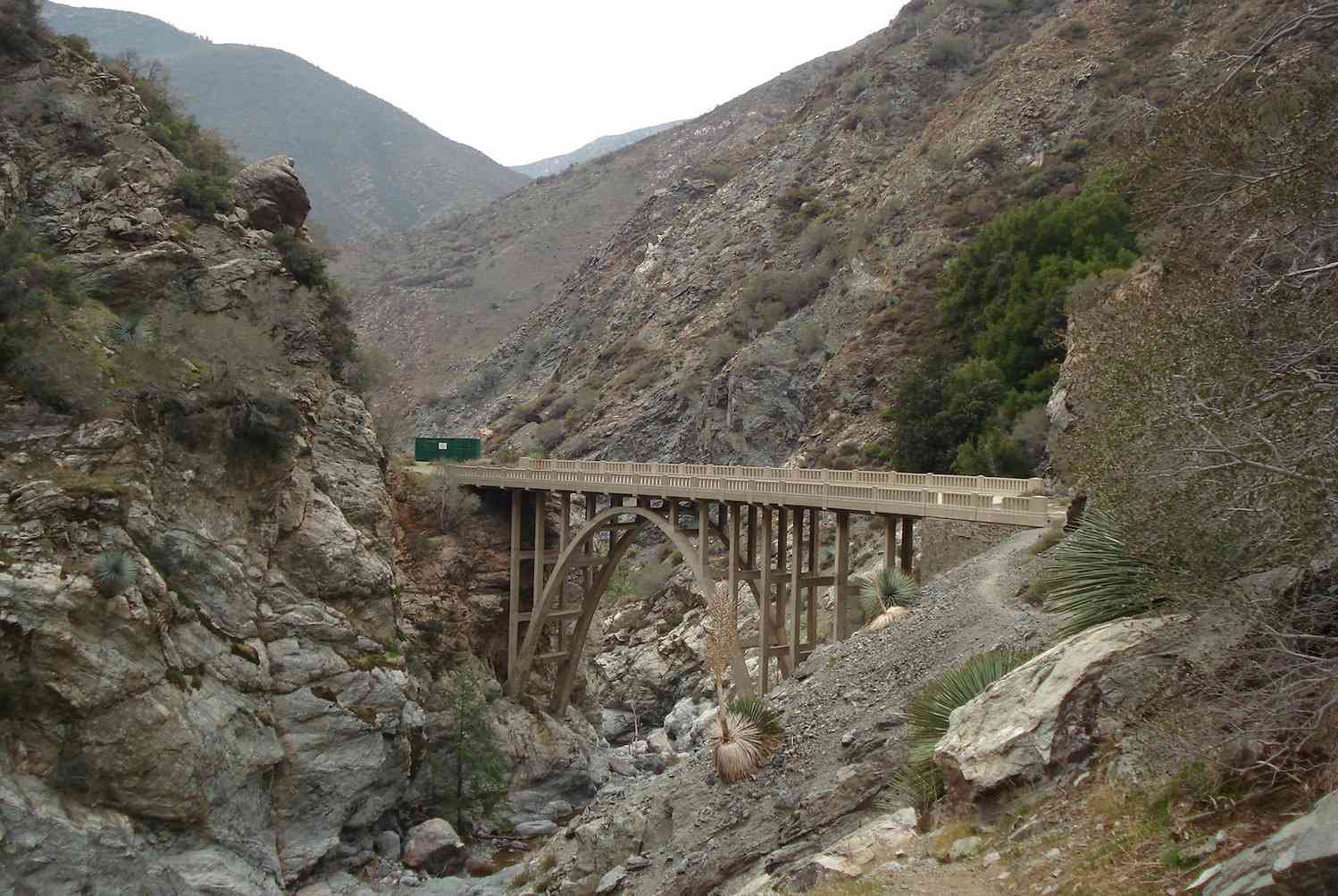 The arched Bridge to Nowhere crossing a dry creek bed among rocky slopes