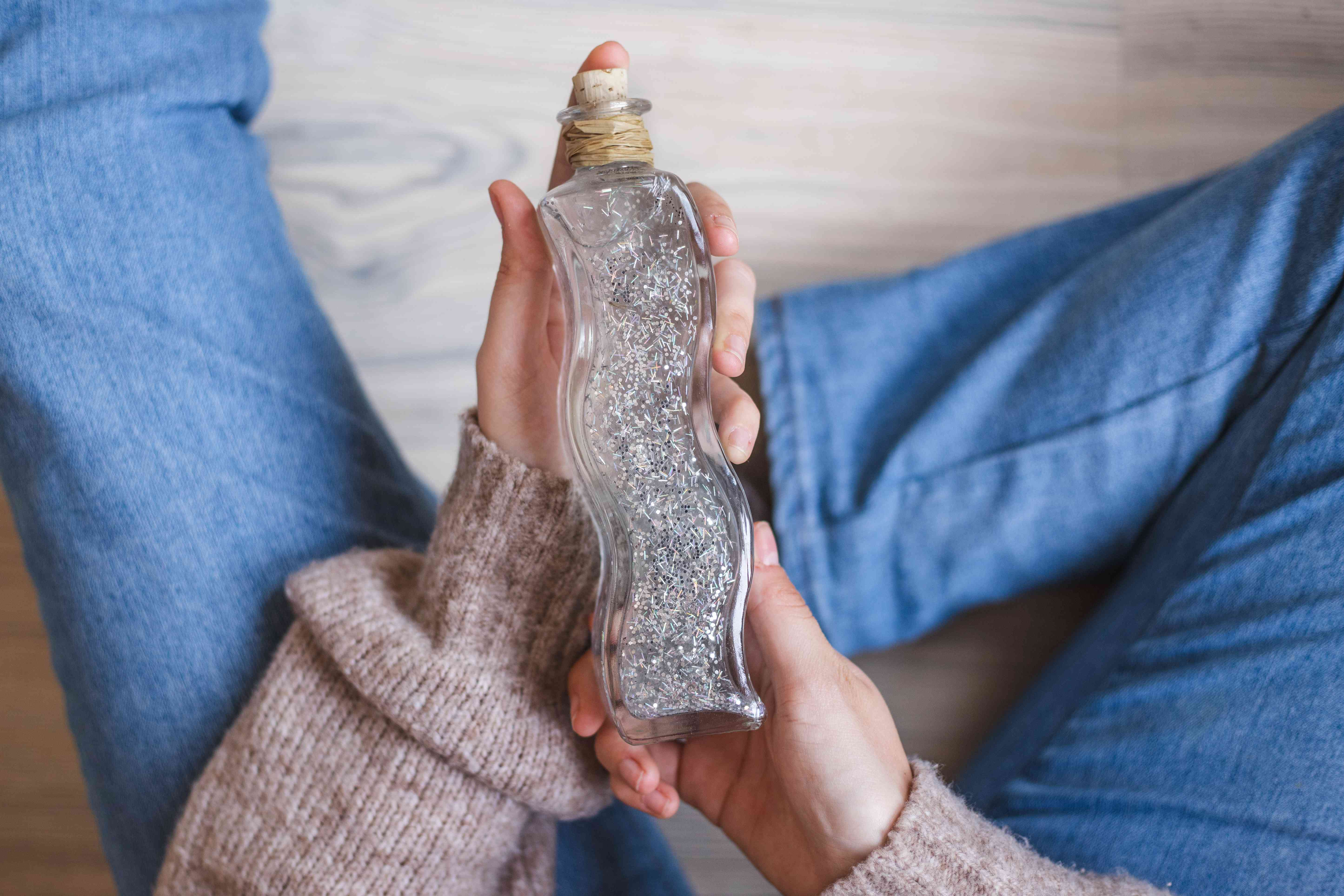 person sits on floor cradling a glass bottle filled with gooey sparkle gel for relaxation