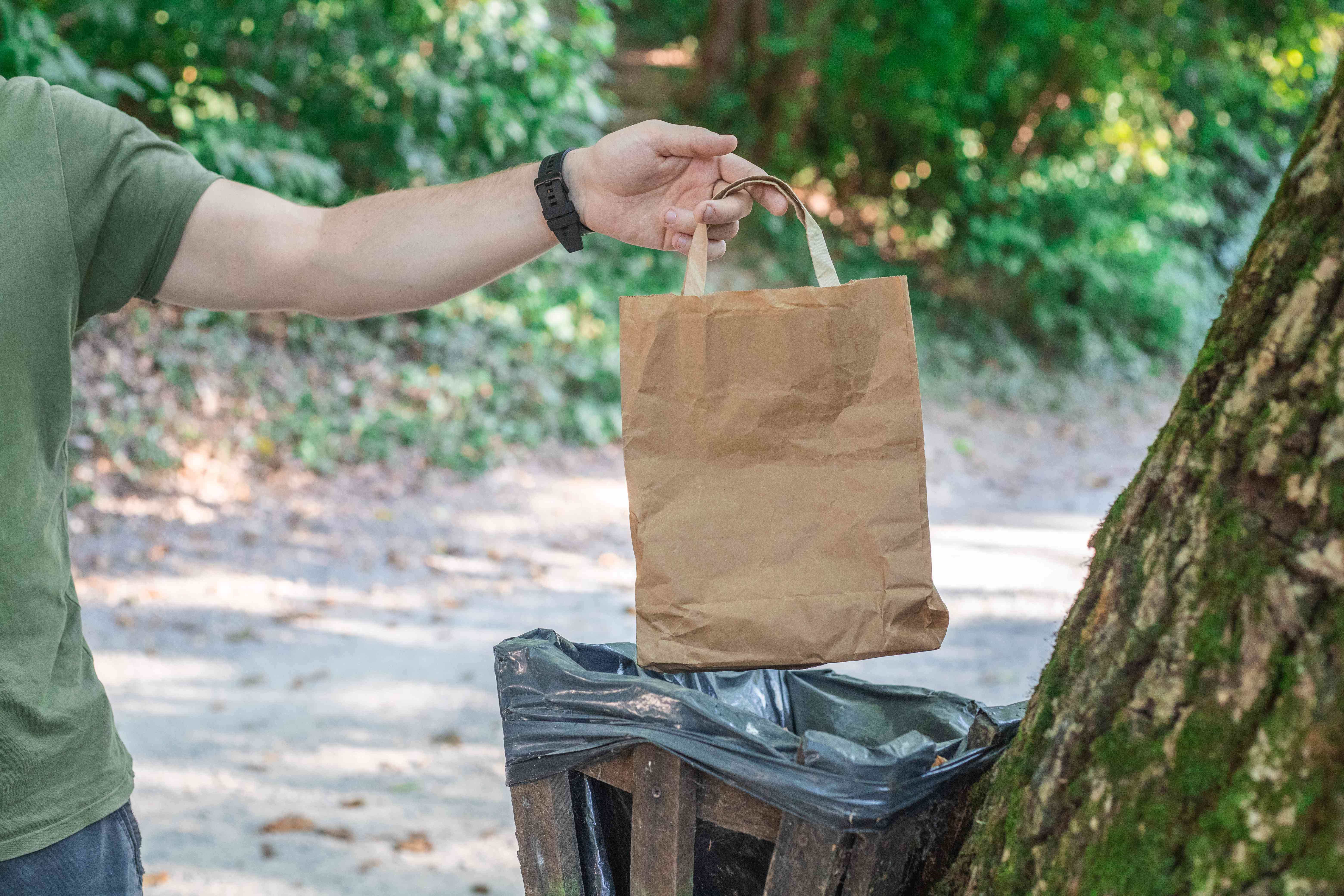 person disposes of brown paper bag in outdoor trashcan to avoid littering