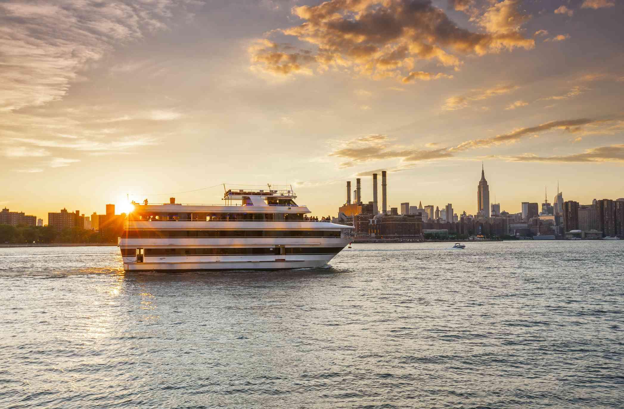 Cruise ship against New York City skyline at sunset