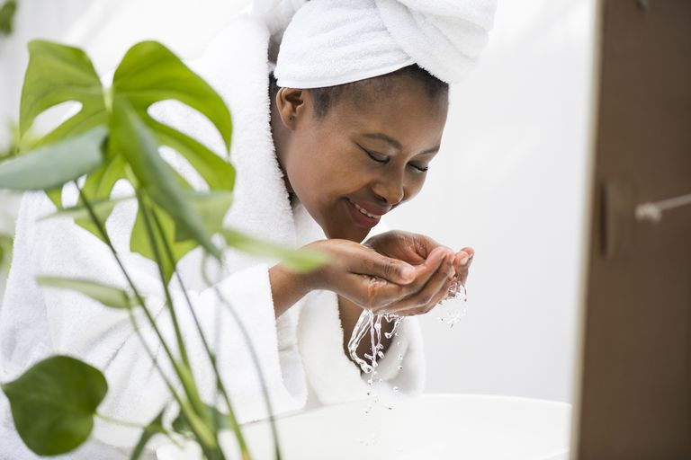 A Black woman with a towel on her head washing her face beside a plant.