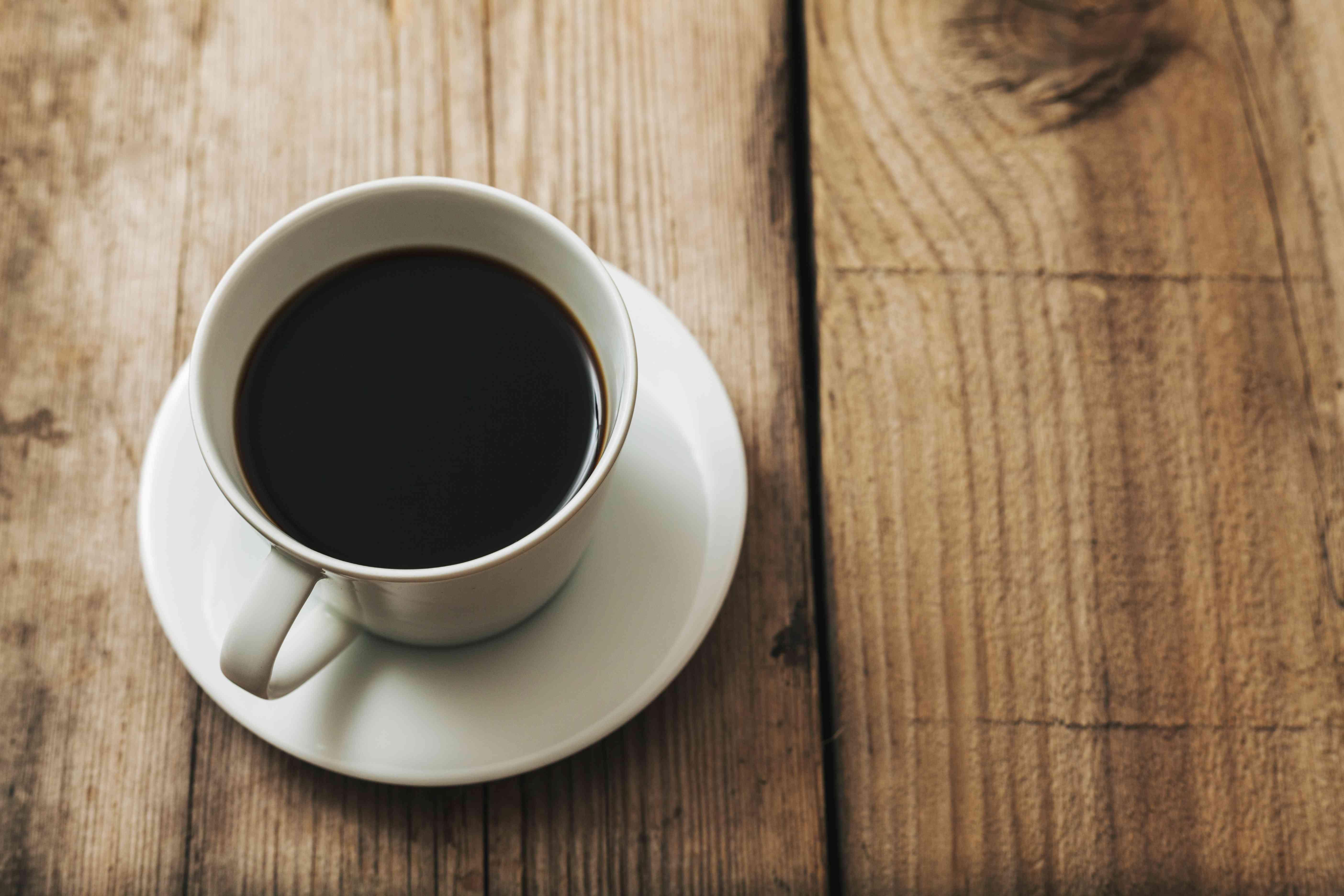 Cup of black coffee on wood