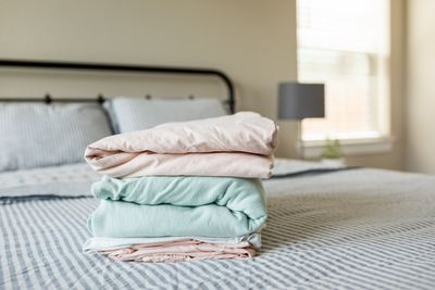 neatly folded bed sheets sit on top of made up bed in bedroom